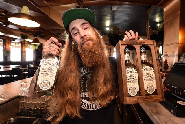 """<img alt=""""mixologist AJ Snetler holds up bottles of Fortaleza Tequila"""">"""