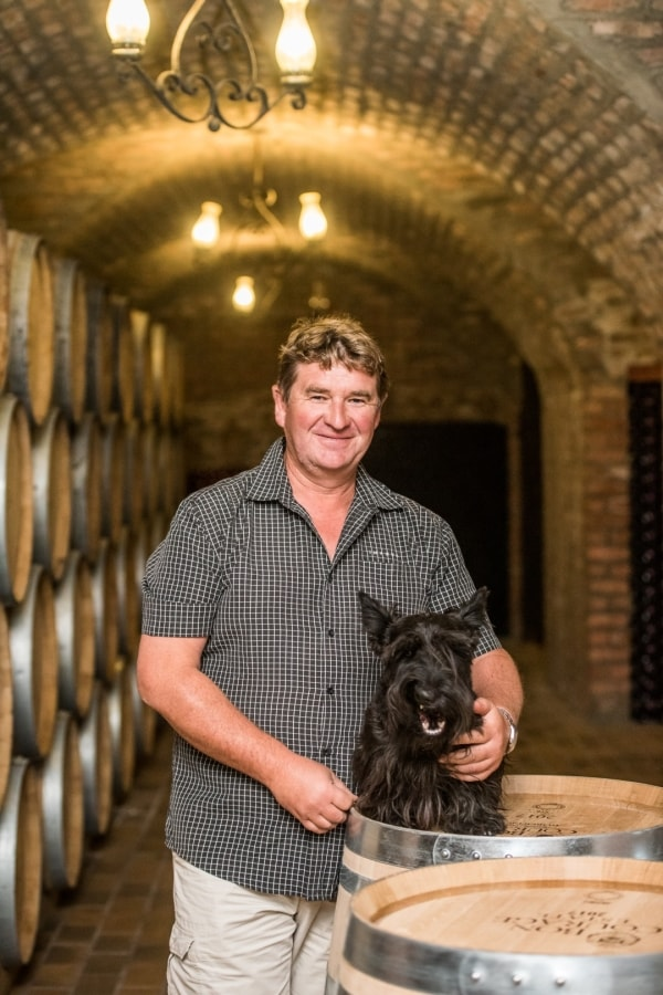 "<img alt=""Jacques Bruwer Maker of Bon Courage MCC holds dog in wine cellar"">"